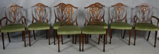 A set of eight Georgian style mahogany dining chairs with carved shield backs on tapering square