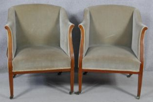 A pair of Edwardian mahogany and satinwood inlaid upholstered tub armchairs on square tapering