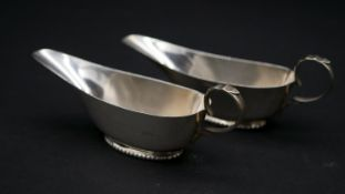 A pair of Victorian sterling silver sauce boats by Williams Ltd. With foliate design handles and