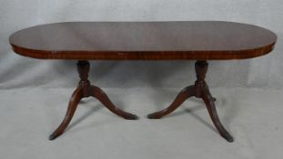 A Georgian style mahogany twin pillar dining table with extra leaf on reeded tripod swept