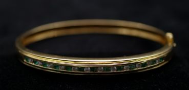 An 18 carat yellow gold, emerald and diamond bangle. Set with thirteen round mixed cut emeralds with