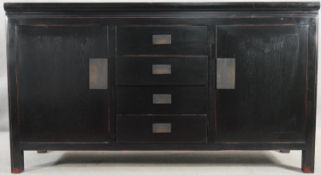 A black lacquered Chinese style sideboard with central drawers flanked by cupboards on block