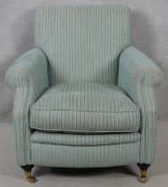 A contemporary 19th century style upholstered armchair on turned mahogany bun supports terminating