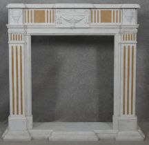 A Classical style marble fire surround and hearth with carved urn decoration to the frieze flanked