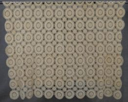 A cream vintage hand crocheted bed throw with stylised repeating floral design. L.218 W.163cm