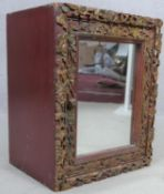 A carved polychrome Eastern teak cabinet with mirrored door. H.43 W.35 D.26cm