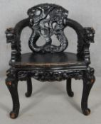 A Chinese ebonised armchair with carved dragon mask arms and panel seat on floral decorated cabriole