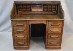 A 19th century oak roll top desk with S shaped tambour front enclosing interior fitted with numerous