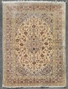 A Persian Kashan with central floral medallion and scrolling meandering foliate design contained