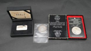 A cased Wonders of the World silver ingot with certificate, a 1983 Olympic US silver dollar proof