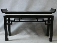 A contemporary Chinese style console table with tray top above pierced frieze on square supports.