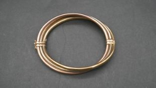 A hollow three colour twist 9ct gold bangle with clip and loop clasp. Hallmarked. D.8cm, 15.5g