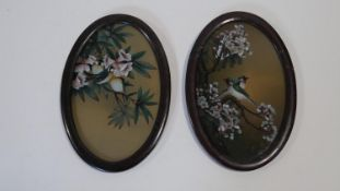 Two oval framed and glazed Japanese acrylic on glass paintings of birds in blossom trees. H.30 W.