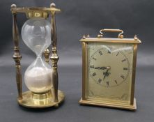 A vintage brass cased hourglass and a battery powered brass mantel clock with carrying handle. H.