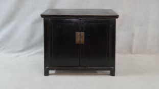 A lacquered Chinese side cabinet with panel doors and brass fittings enclosing a pair of drawers