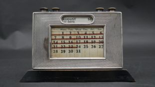 An antique ebonised wooden backed silver desk calendar with five knobs for adjusting month, day