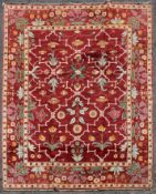 A Moughal design carpet with repeating stylised floral pattern across a madder ground within foliate