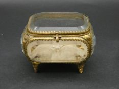 A French antique bevelled glass gilt metal jewellery box with silk button cushion to base. H.8 L.