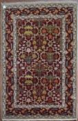 A Moughal design rug with repeating scrolling foliate design on madder field within stylised