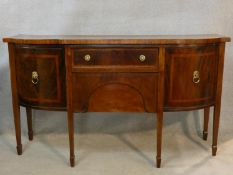 A Georgian mahogany and satinwood crossbanded sideboard of bowed outline fitted with frieze drawer