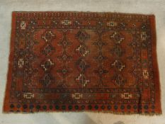 A Shirvan rug with repeating gul motifs across the madder ground contained by multiple stylised