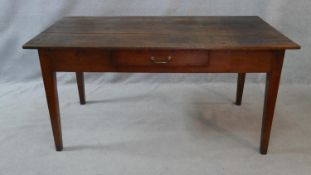A 19th century farmhouse style dining table with an elm planked top above frieze drawer on square
