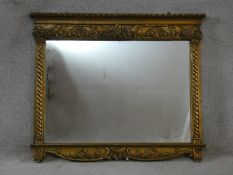 A 19th century gilt and gesso framed overmantel mirror with original plate flanked by spiral twist