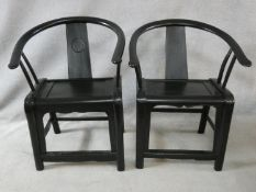 A pair of antique Chinese hardwood hooped back armchairs on rounded stretchered supports. H.90cm