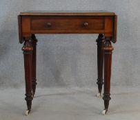 A mid 19th century mahogany writing table with inset leather top and drop flaps with frieze drawer