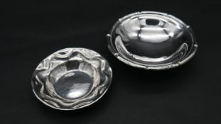 A white metal and Continental silver bowl. One with fluted edge and sitting on three ball feet.