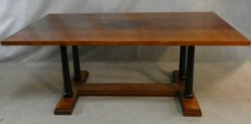 A contemporary teak refectory dining table with central inlaid lozenge raised on circular ebonised