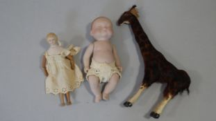 Two antique porcelain dolls, one with jointed wooden body, legs and arms and an antique fur