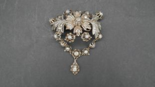 A Georgian style white metal stylised foliate and floral design brooch with articulated drop. Set