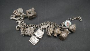 A vintage white metal (tested silver) curb link charm bracelet with fifteen white metal and silver