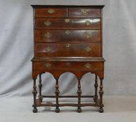 A Queen Anne walnut and feather banded chest on stand with two short and three long graduated
