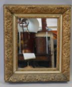 A 19th century gilt wood and gesso wall mirror in floral decorated frame. H.59 W.51cm