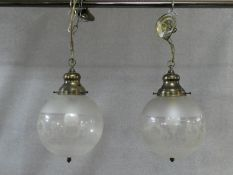 A pair of etched and frosted glass ceiling light pendants of globular shape. H.42 D.50cm