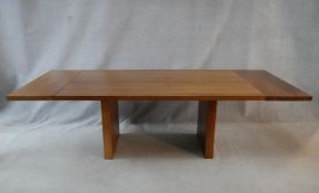 A contemporary hardwood dining table with extension leaf to each end raised on block trestle