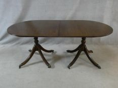 A Regency style mahogany and satinwood strung twin pillar dining table on swept quadruped supports