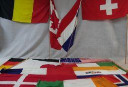 A miscellaneous collection of thirteen various vintage national flags along with three flag poles.