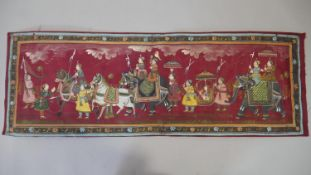 An Indian painting on silk, a Royal procession within a floral border. H.34 W.100cm
