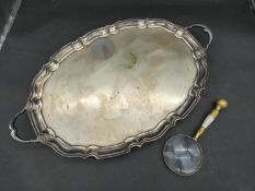 A large twin handled silver plated serving tray with scalloped ridge edges and foliate form feet
