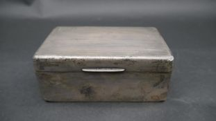 An Art Deco cedar lined silver cigarette box with linear engine turned decoration and rectangular