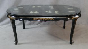A Chinese black lacquered dining table with applied figural decoration and hand painted detail on