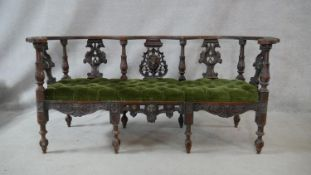 A 19th century Continental oak canape with pierced and carved splats with griffin and lion's mask