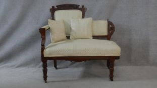 A late 19th century carved walnut small chaise in polka dot upholstery raised on turned tapering