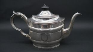 A Georgian silver tea pot with engraved laurel leaf decoration and Greek key design circular