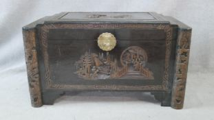 A Chinese camphor coffer with all over carved figural decoration. H.58.5 W.103.5 D.54cm