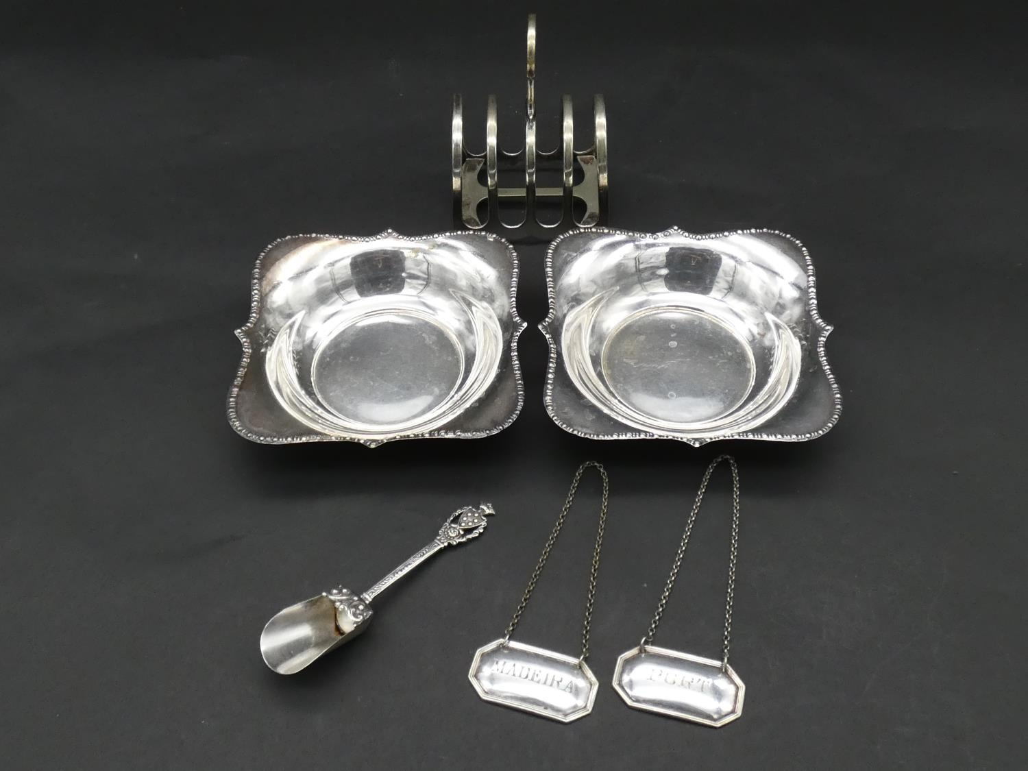 A collection of silver and silver plate items. Including a toast rack, two floral design dishes a