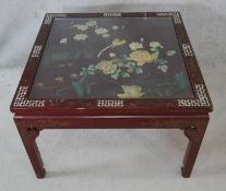 A Chinese black lacquered coffee table with bevelled plate glass drop in top, applied bird and
